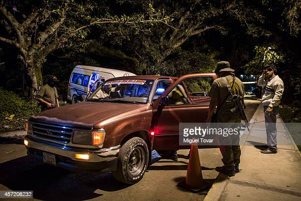 A masked member of the community police force inspect a car at a check point outside the Raul Isidro Burgos de Ayotzinapa Teachers College on October...