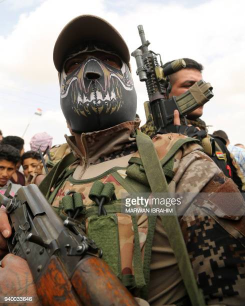 A masked member of the Iraqi federal police stands guard while the governor of Kirkuk speaks to families from the Hawija region who were displaced by...