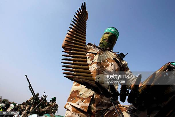 Masked member of the militant group Ezzedine al-Qassam Brigades, Hamas's armed wing, parades in Rafah, southern Gaza Strip, on November 14 during an...