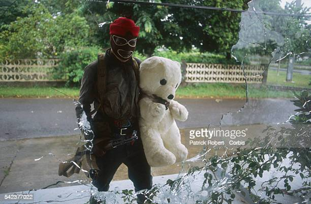 A masked member of the National Patriotic Front of Liberia holds onto a large stuffed teddy bear Responding to years of government corruption and...