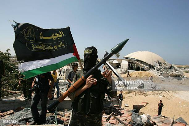 A masked member of the Palestinian militant group Islamic Jihad poses for photographers during a media conference near the demolished synagogue in...
