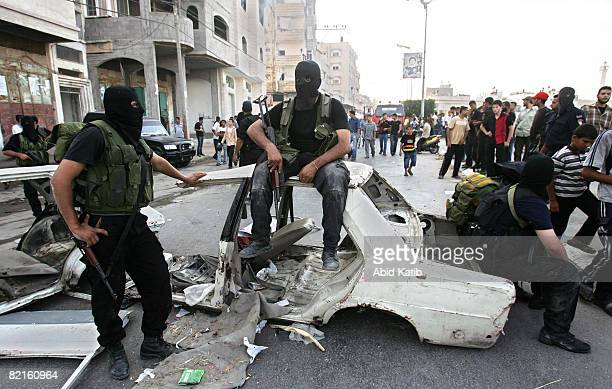 Masked members of Hamas take a rest during clashes between rival forces of Hamas and Fatah movements in the Shujaia neighborhood August 2 2008 in...