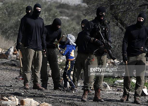 TOPSHOT Masked members of the Israeli security forces briefly detain a Palestinian boy during clashes following a demonstration against the...