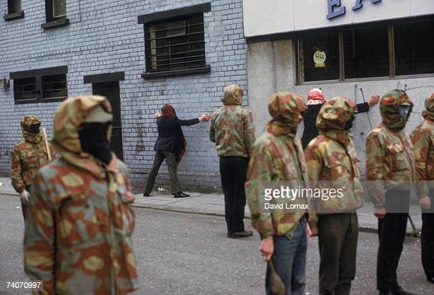 Masked members of the loyalist paramilitary organization the Ulster Defence Association detaining two hooded IRA suspects Belfast Northern Ireland...