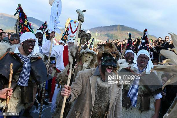 Masked men or Vijanera bring in another dressed as a bear during the carnival in Silio northern Spanish province of Cantabria on January 4 2015 The...