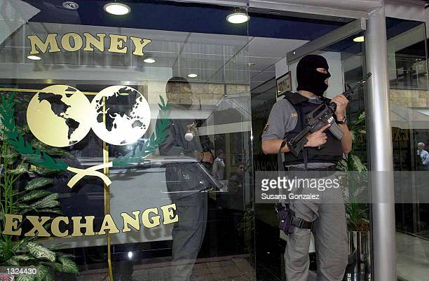 Masked Mexican police officer stands guard during a raid of a currency exchange store June 21 2001 in Mexico City The raid was part of Operation...