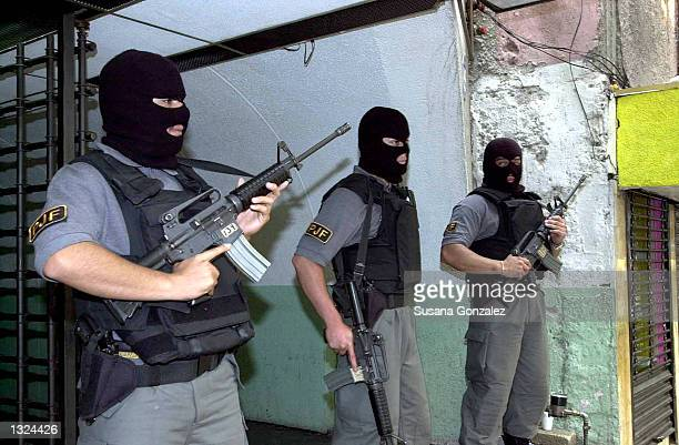 Masked Mexican police stand guard during a raid of a currency exchange store June 21 2001 in Mexico City The raid was part of Operation Marquis which...