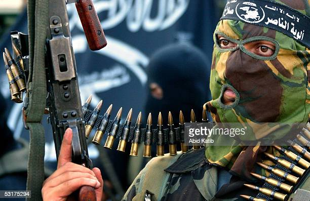 Masked militant takes part in a march during an anti-Israel rally June 30, 2005 at the Jabalya refugee camp in the northern Gaza Strip. Palestinian...