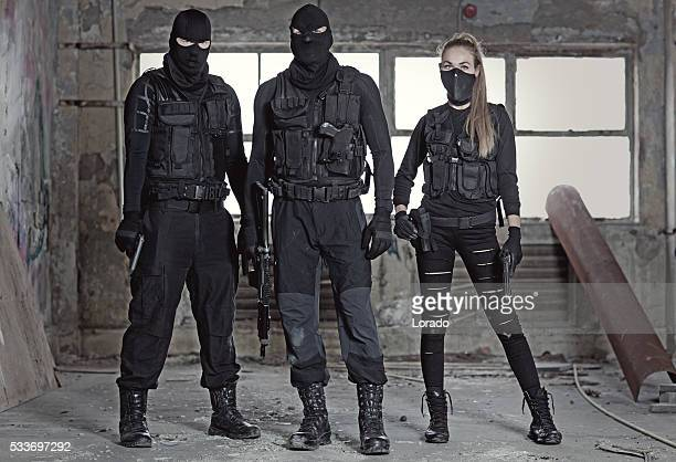 Masked military swat team members holding weapons in abandoned warehouse