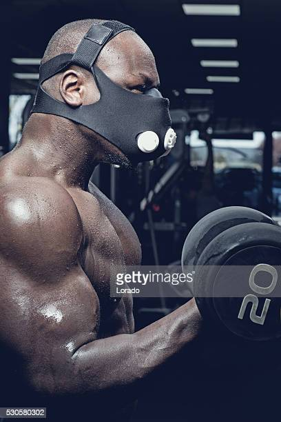 Masked muscled black male exercising with weights in a gym