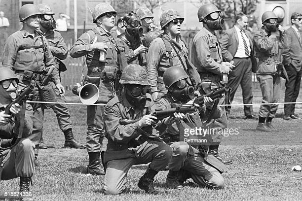 Masked national guardsmen fire barrage of tear gas into crowd of demonstrators on campus of Kent State University May 4th. When the gas dissipated,...