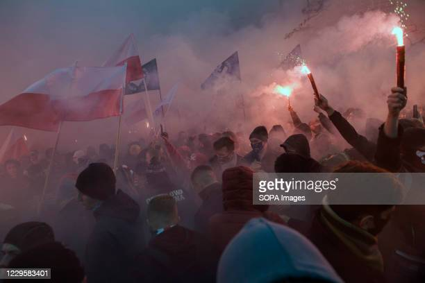 Masked nationalists burning flares during Independence Day. Thousands took part in an annual far-right march in Warsaw to mark Polands Independence...