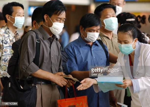 A masked nurse asks passengers to fill in a list stating all departure transit and arrival cities at Chiang Kaishek international airport in Taoyuan...