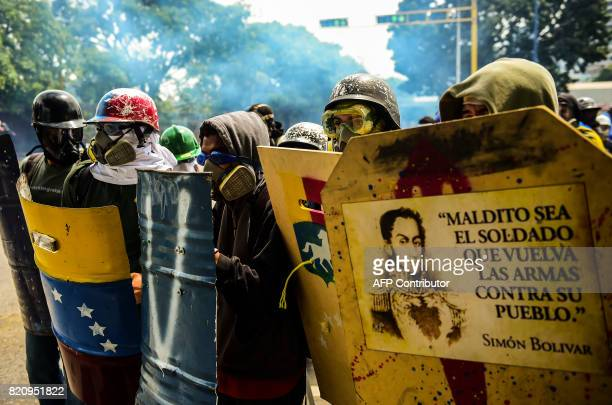 TOPSHOT Masked opposition activists hide behind shields as they clash with riot police during a march towards the Supreme Court of Justice in an...
