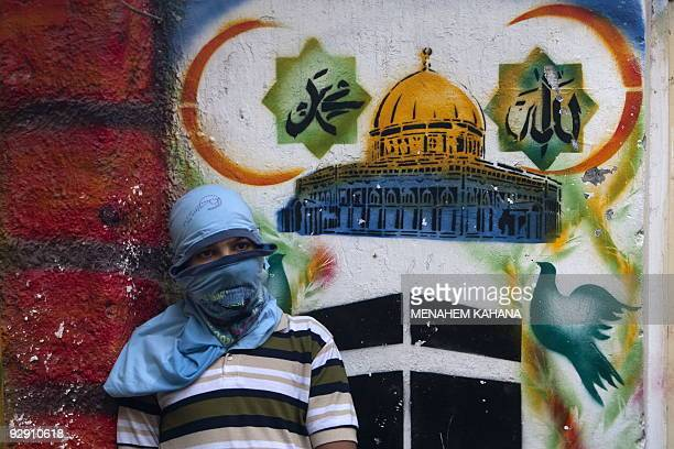 A masked Palestinian boy rests against a wall with religious graffiti and the name of Allah and Islam's Prophet Mohammed written in Arabic above...