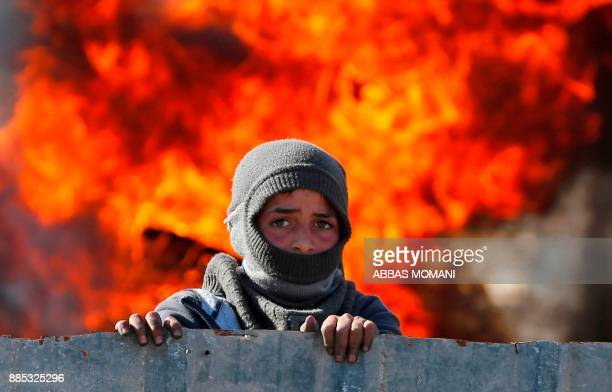 A masked Palestinian boy stands in front of flames during clashes with Israeli soldiers at the entrance of the northern village of Qusra in the...