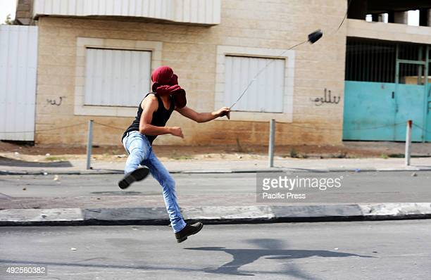 A masked Palestinian demonstrator hurls a rock towards the Israeli military checkpoint in Bethlehem West Bank A 27yearold Palestinian man was shot...