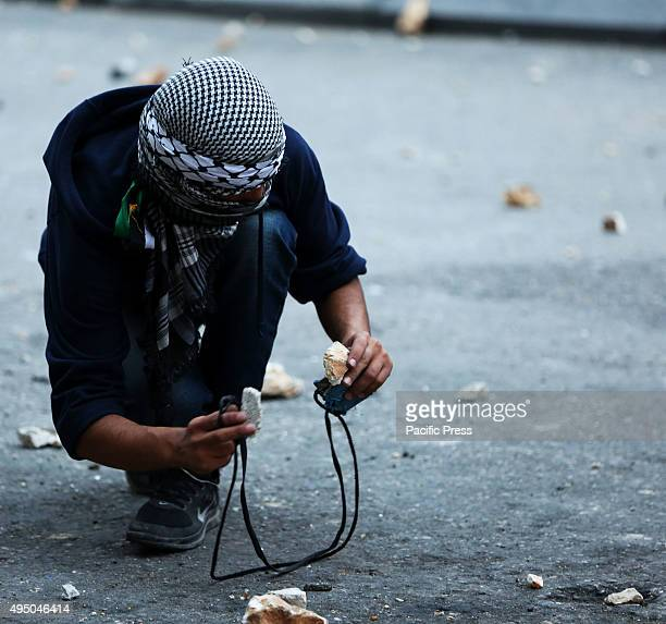 A masked Palestinian demonstrator picks up rocks during a demonstration in the West Bank city of Bethlehem Following another Day of Rage across the...