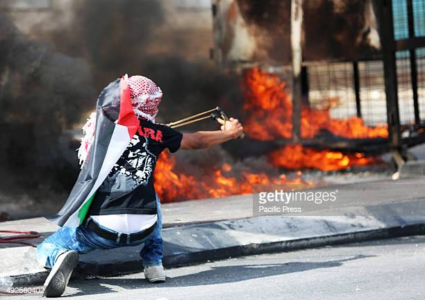 A masked Palestinian demonstrator uses a slingshot to shoot marbles at an Israeli military checkpoint in the West Bank city of Bethlehem A 27yearold...