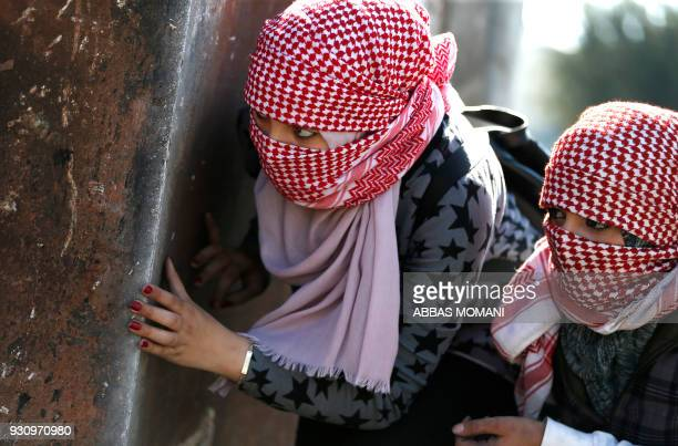 TOPSHOT Masked Palestinian demonstrators hide behind a metal plate during clashes with Israeli soldiers on March 12 2018 in the West Bank town of...