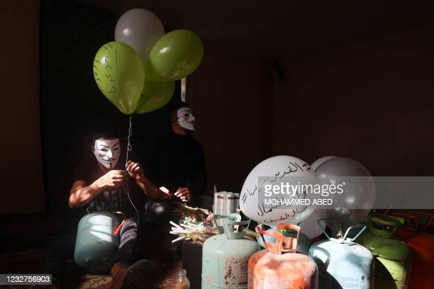 Masked Palestinian followers of the Hamas movement prepare incendiary balloons with anti-Israel slogans written on them, near Beit Lahia in the Gaza...