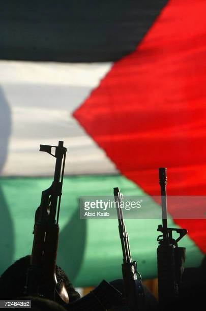 Masked Palestinian gunmen from the Fatah movement hold their weapons in front of the palestinian flag during a march in support for Palestinian...