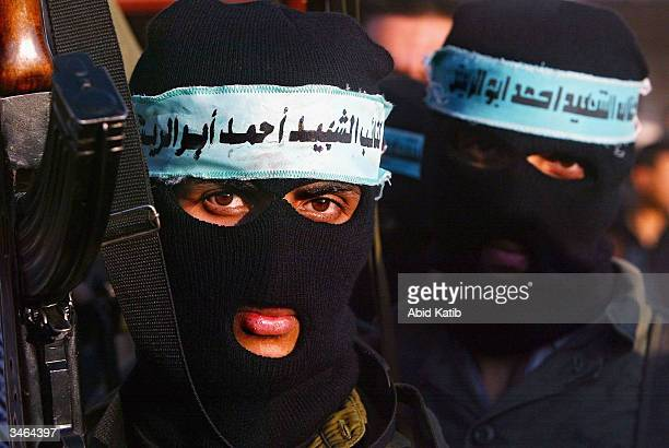 Masked Palestinian gunmen from the Fatah movement march in support of Palestinian leader Yasser Arafat on April 242004 in the Nussirat refugee camp...