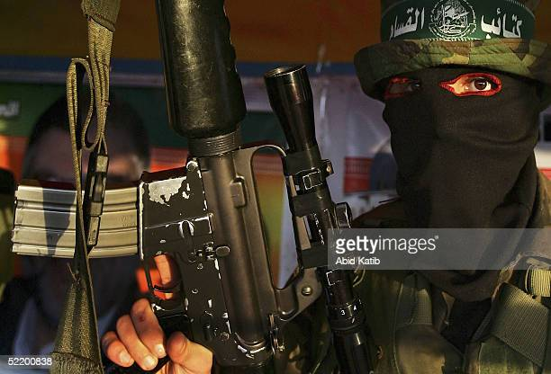 Masked Palestinian Hamas fighters march during an honouring celebration for fighters who were killed by the Israeli Army February 15 2005 in Deir...