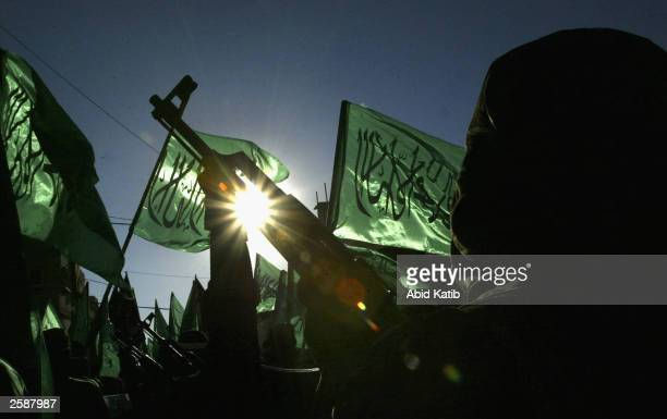 Masked Palestinian Hamas militants march during a protest demonstration at the Rafah refugee camp October 13, 2003 in the Southern Gaza Strip....