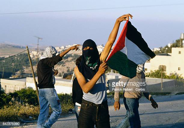 A masked Palestinian man holds up a Palestinian flag during a riot in Shufat Jerusalem The riot is in response to a shooting by a discharged Israeli...