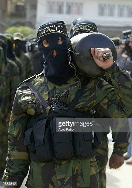 A masked Palestinian member of the Islamic Jihad Movement dressed as a suicide bomber and carrying a bomb marches during a rally October 31 2003 in...