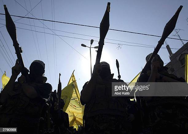 Masked Palestinian members of the Al-Aqsa Martyrs Brigades, a militant group linked to Palestinian leader Yasser Arafat's Fatah movement, carry their...