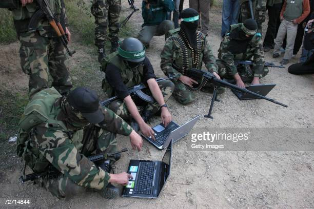 Masked Palestinian members of the AlQassam brigade the military wing of The Islamic Resistance Movement Hamas use laptops during a military exercise...
