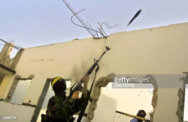 Masked Palestinian militant fires a homemade rocket from his gun towards an Israeli tanks in Rafah Refugee camp in the Gaza Strip 10 September 2003....