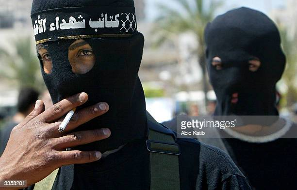 A masked Palestinian militant from the Al Aqsa martyrs brigade a group affiliated with Yasser Arafat's Fatah movement smokes during antiIsraeli rally...