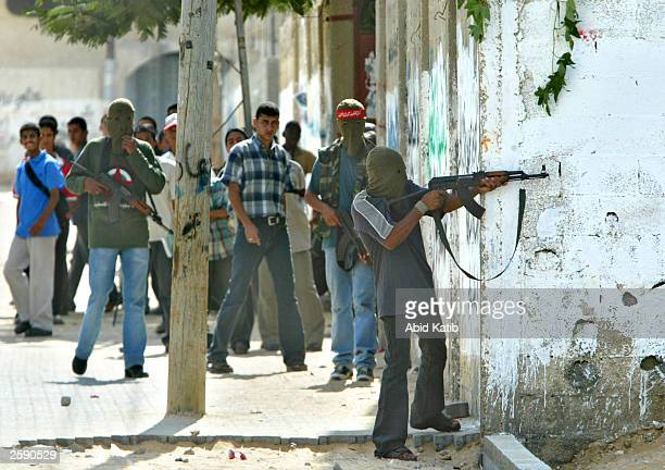A masked Palestinian militant using an AK47 automatic rifles open fire towards Israeli forces on the streets of the Al Salam area October 14 2003 in...