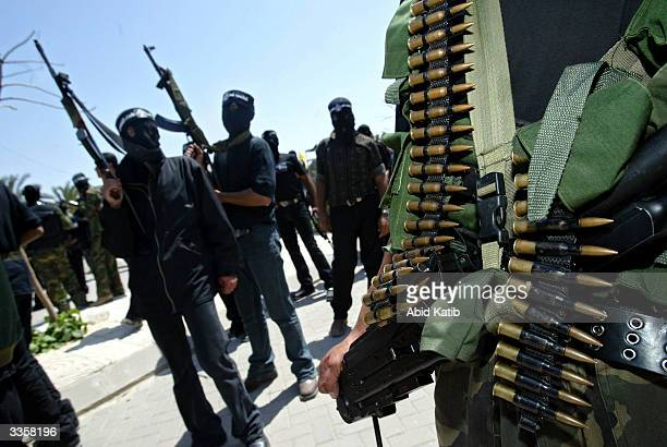Masked Palestinian militants from the Al Aqsa martyrs brigade a group affiliated with Yasser Arafat's Fatah movement hold their weapons during...