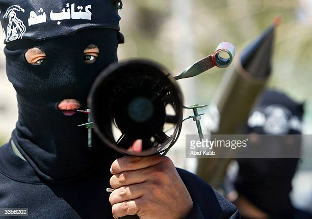 Masked Palestinian militants from the Al Aqsa martyrs brigade, a group affiliated with Yasser Arafat's Fatah movement, hold their weapons during...