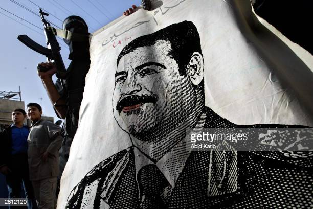 Masked Palestinian militants from The AlAqsa brigade a link of Yasser Arafat 's Fatah movement hold their guns and pictures of former Iraqi President...