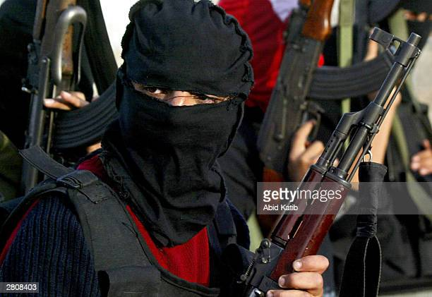 Masked Palestinian militants hold their guns during a demonstration held to mark the 36th anniversary of the creation of the Popular Front for the...