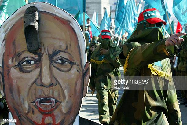 Masked Palestinian militants of the Islamic group of Hamas march as they carry a portrait depicting Israeli Prime Minister Ariel Sharon as a vampire...