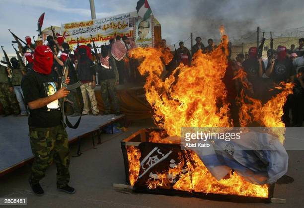 Masked Palestinian militants of the Popular Front for the Liberation of Palestine burn a coffin symbolizing the unofficial peace plan known as the...