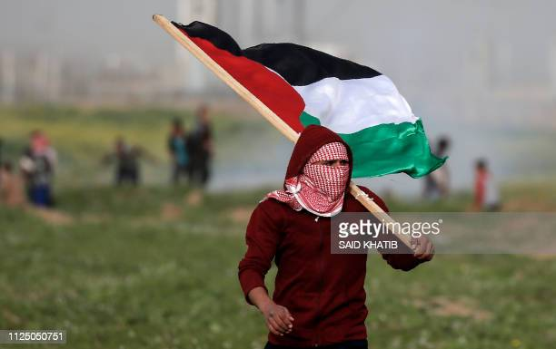 A masked Palestinian protester carries the national flag during clashes with Israeli forces following a demonstration near the fence along the border...