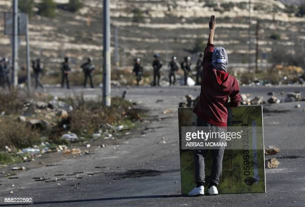 TOPSHOT A masked Palestinian protester gestures during clashes with Israeli troops near an Israeli checkpoint in the West Bank city of Ramallah on...