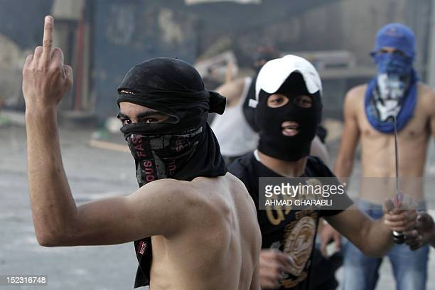 A masked Palestinian protester makes an obscene gesture at Israeli security forces during clashes that erupted after a demonstration against an...