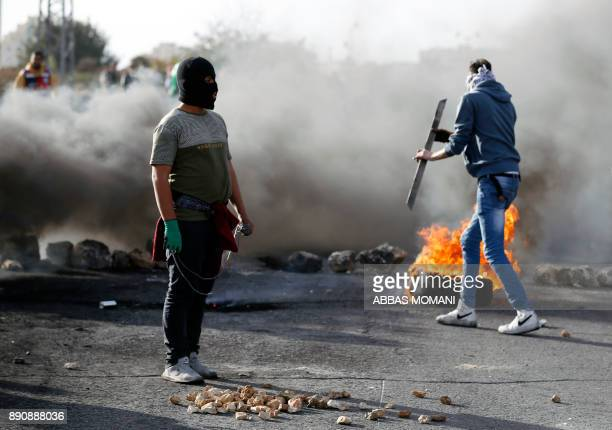 A masked Palestinian protester stands amidst smoke from flaimg tires and tear gas fumes during clashes with Israeli forces in the West Bank city of...