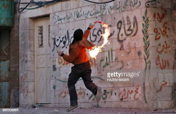 A masked Palestinian protester throws a molotov cocktail during clashes with Israeli soldiers behind a checkpoint in the city centre of the West Bank...