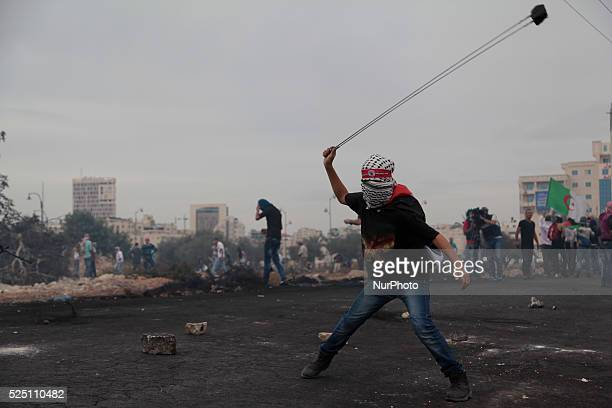 Masked Palestinian protester throws rocks using slinger on Israeli army during clashes near Ramallah Clashes erupted between hundreds of Palestinian...