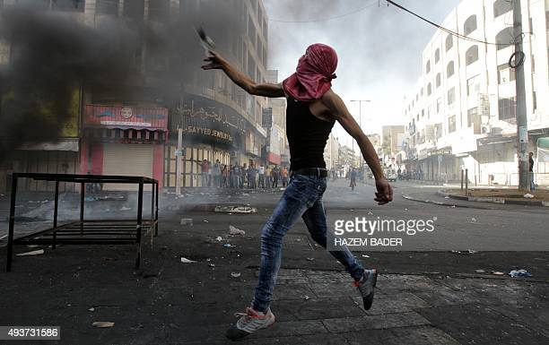 A masked Palestinian protester throws stones during clashes with Israeli security forces in the occupied West Bank city of Hebron on October 22...
