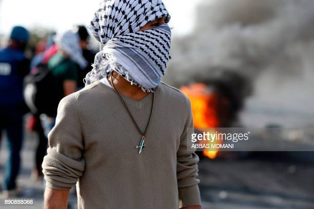 A masked Palestinian protester wearing a necklace showing a map of mandatory Palestine coloured with the Palestinian flag and with a crossed key...